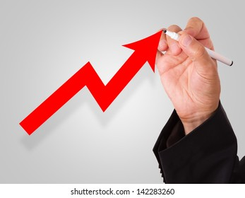 Business hand draws red graph arrow.