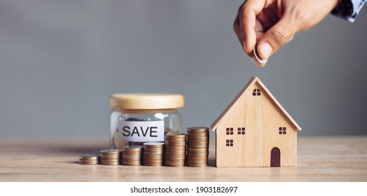 Business hand holding home with Buy or Rent, copy space. Property investment and house mortgage financial concept, Hand putting money coin stack with wooden house.