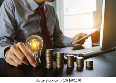 business hand holding lightbulb with using laptop computer and money stack in office. idea saving energy and accounting finance concept  in morning light