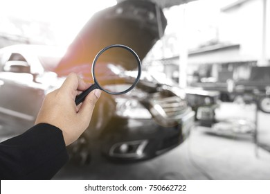 Business hand holding magnification with car background