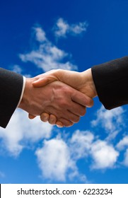 A business hand shake on a summer clouds background