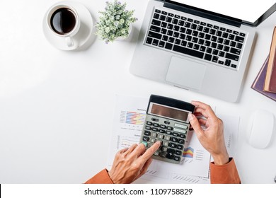 Business hand working with calculator,laptop and financial data on white desk table in office.Top view with copy space,Flat lay.