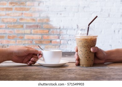Business hand's holding coffee cups on wooden table in coffee shop.