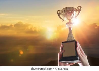 Business hands holding trophy cup on sunset background.