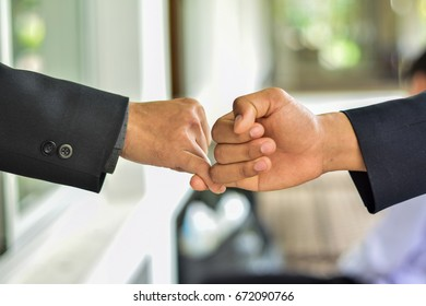 business  Hands shake ,Usually people with higher positions. The board usually extends it first. accept or yield to a superior force or to the authority or will of another person.