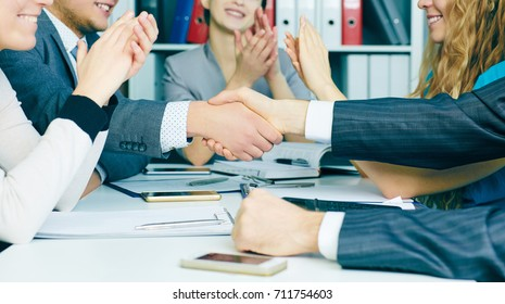 Business handshake. Close-up of two young man shaking hands with smile while sitting at office with their beautiful coworker. 