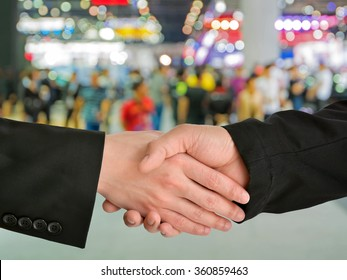 Business handshake closing a deal with blur background of people in exhibition show