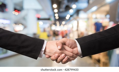 Business handshake closing a deal with blur background of people