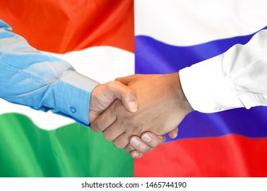 Business handshake on the background of two flags. Men handshake on the background of the Hungary and Russia flag. Support concept