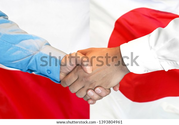 Business handshake on the background of two flags. Men handshake on the background of the Poland and Japan flag. Support concept