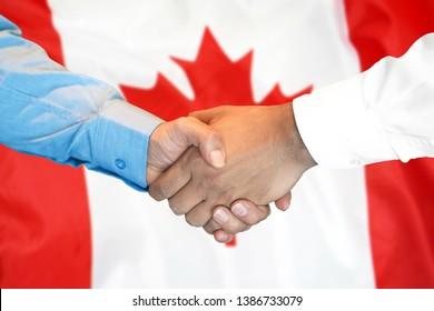 Business handshake on Canada flag background. Men shaking hands and Canadian flag on background. Support concept