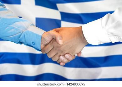 Business handshake on Greece flag background. Men shaking hands and Greece flag on background. Support concept