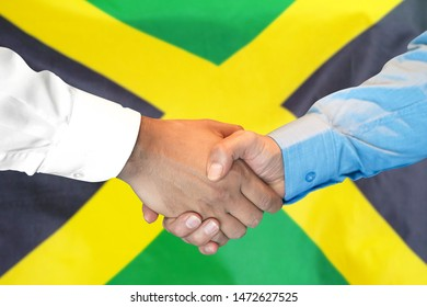 Business handshake on Jamaica flag background. Men shaking hands and Jamaica flag on background. Support concept