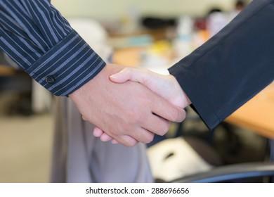 Business handshake on meeting room background