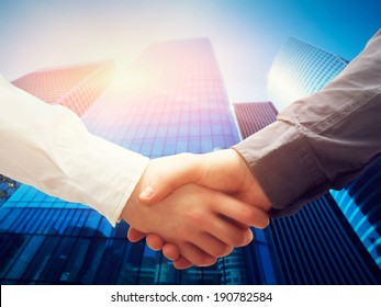Business handshake on modern skyscrapers background. Deal, success, contract, cooperation concepts