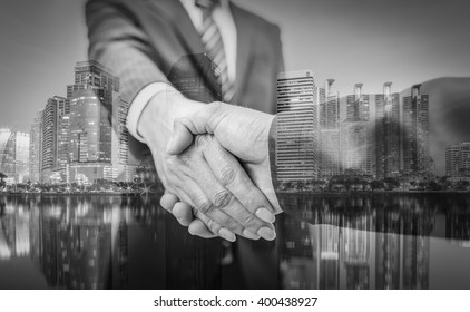 Business handshake and business people on city background ,  black and white.