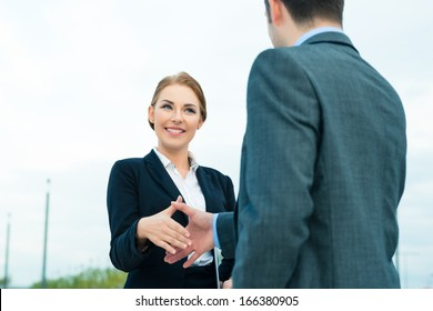Business handshake - two businesspeople shaking hands to conclude deal or agreement