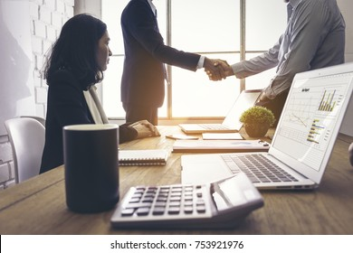Business handshake of two men. To show agreement and satisfaction in showing the cooperation between organizations. The businessman Asian girl witnessed.
