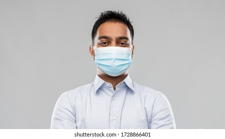 business, healthcare and people concept - portrait of indian man in shirt wearing face medical mask for protection from virus disease over grey background