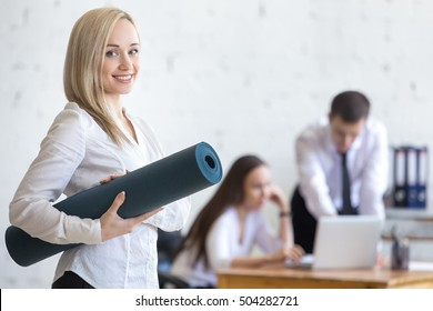 Business and healthy lifestyle concept. Beautiful sporty young office woman finished her work and going at fitness training. Cheerful model posing with exercise mat and friendly smiling at camera