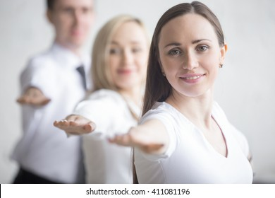 Business and healthy lifestyle concept. Portrait of young office workers standing in yoga pose at workplace. Smiling business people doing Warrior II posture, Virabhadrasana 2 pose on break time