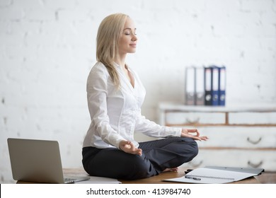 Business and healthy lifestyle concept. Portrait of young office woman sitting cross-legged in half lotus yoga pose at workplace. Smiling business lady meditating after finishing her work