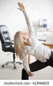 Business and healthy lifestyle concept. Portrait of young office woman standing in yoga pose at workplace. Happy beautiful business lady doing Extended Side Angle posture on her break time