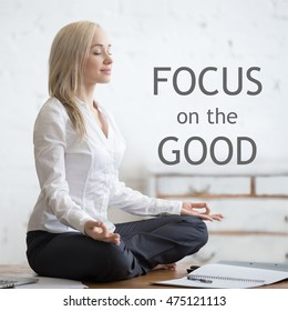 """Business and healthy lifestyle concept. Portrait of young office woman sitting cross-legged in lotus yoga pose at workplace. Smiling beautiful lady meditating. Motivational phrase """"Focus on the good"""""""
