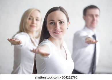 Business and healthy lifestyle concept. Portrait of young corporate workers standing in yoga pose at workplace. Attractive cheerful business people practicing Warrior II posture together on break time