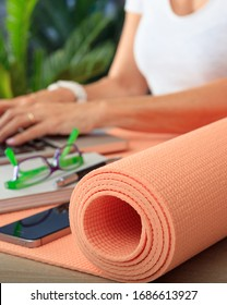 Business and healthy lifestyle concept. Yoga mat on an office desk closeup view, fit woman at workplace
