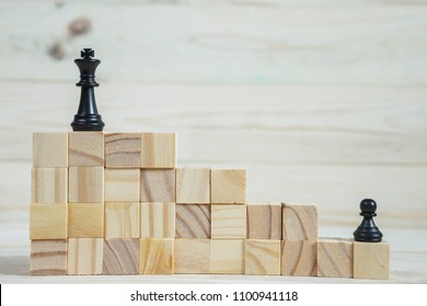 Business hierarchy. Strategy concept with chess pieces. Chess standing on a pyramid of wooden building blocks with the king at the top. copy space.