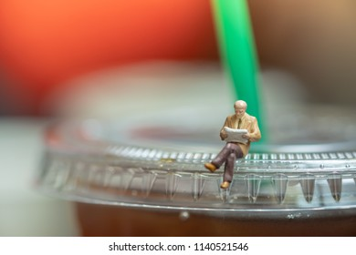 Business, Hobby, waiting and relaxation concept. Business man miniature figure sitting and reading on take away plastic cup of iced black coffee.