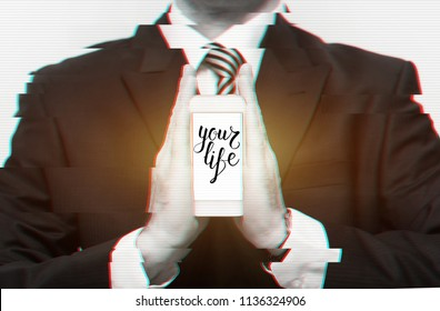 Business holding telephone with description 'Your Life' on screen in his hands. Concept of virtual life. Glitch effect.