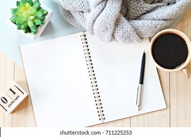 Business, holiday or new year planning concept : Desk table with scarf, notebook paper, cube calendar and coffee cup, Top view or flat lay with copy space ready for adding or mock up