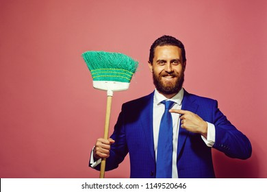business and home, formal fashion, handsome man or happy businessman with broom on pink background, copy space