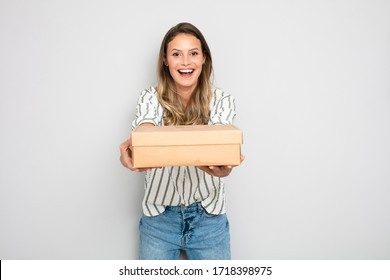 business from home, single happy woman holding a cardboard in hands ready to send it to the one who buy it from the online store