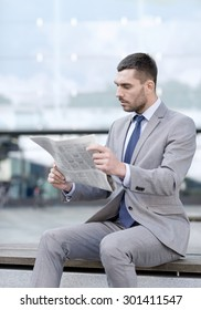 business, hot drinks and people and concept - young serious businessman with newspaper over office building