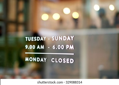 Business hours through a dirty window