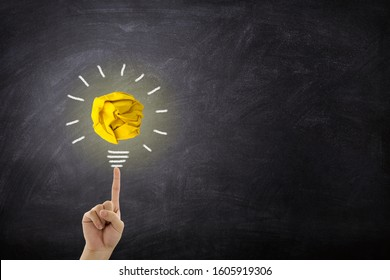 Business Idea Concept : Fingertip touch yellow crumpled paper ball light bulb on chalkboard.