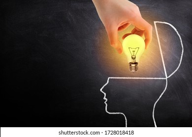Business Idea Concept : Hand holding light bulb lighting grow and putting in brain white chalk doodle on chalkboard.