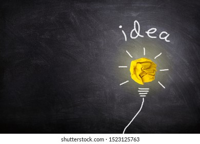 Business Idea Concept : Yellow crumpled paper ball light bulb lighting grow around on chalkboard.