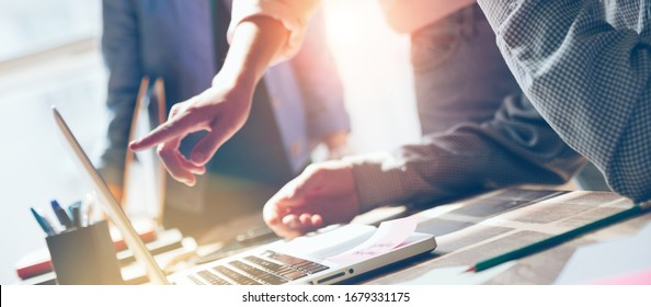 Business idea discussing. Startup team working with digital project. Laptop and paperwork on the table. Lens flares effect, film effect. Wide screen. Panoramic