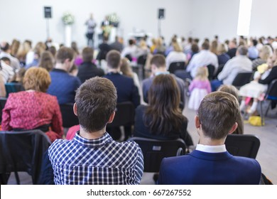 Business Ideas. People Sitting In Lines During a Conference While Female Host Speaking on Stage. Horizontal Image