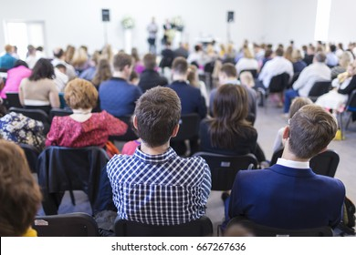 Business Ideas. People Sitting In Lines During a Conference While Female Host Speaking on Stage. Horizontal Image Orientation