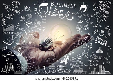 Business ideas.Light bulb on hand with freehand drawing business doodles set,