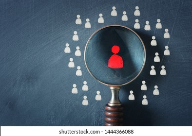business image of magnifying glass with people icon over chalkboard background, building a strong team, human resources and management concept
