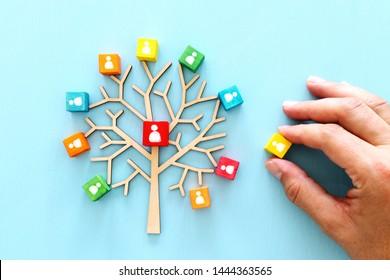 Geschäftsbild eines Holzbaums mit Menschen-Symbolen auf blauem Tisch, Humanressourcen und Management-Konzept