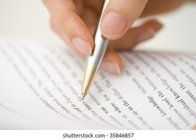 BUSINESS IMAGE-a hand checking the document with a silver pen