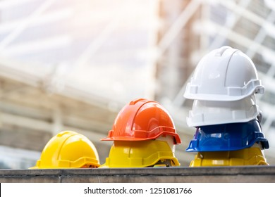 Business Industrial Safety Health Employee Concept. white, yellow and blue hard safety helmet hat for safety project of workmen as engineer or worker, on concrete floor on construction site or city