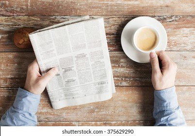 business, information, people and mass media concept - close up of male hands with newspaper, muffin and coffee cup on table